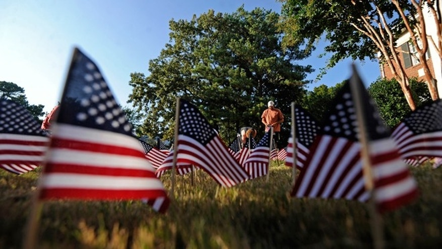 FILE -- Sept. 10, 2014: Members of the Alpha Tau Omega fraternity place American flags in the yard in front of their house on the University of Mississippi campus in Oxford, Miss. The fraternity placed about 3,000 flags for the people killed in the 9/11 attacks.