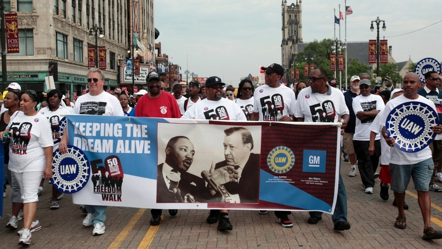 UAW union members carry a banner showing Martin Luther King Jr and labor leader Walter Reuther as they march down Woodward Avenue during the 50th Anniversary Commemorative Freedom Walk in Detroit, Michigan.
