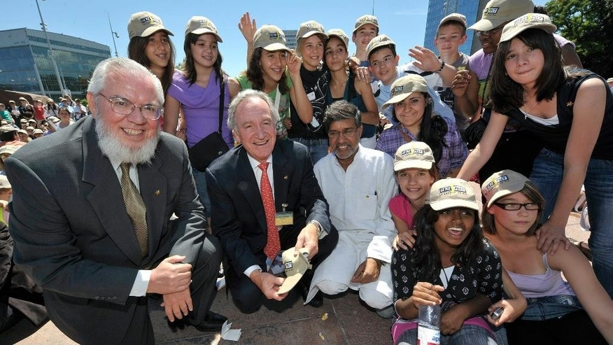 FILE - In this June 12, 2009 file photo, Kailash Satyarthi, , third from left, Indian coordinator of the Global March against child labour, Chilean Juan Somavia, left, director general of the International Labor Organization, Tom Harkin, second from left, senator of Iowa at the Congress of the United States, pose with school children of the Canton of Geneva, during the World Day Against Child Labour at the Place of Nations in front of the European headquarters of the United Nations in Geneva, Switzerland. Children's rights activists Malala Yousafzai of Pakistan and Satyarthi of India were awarded the Nobel Peace Prize Friday, Oct. 10, 2014. (AP Photo/Keystone, Martial Trezzini, File)