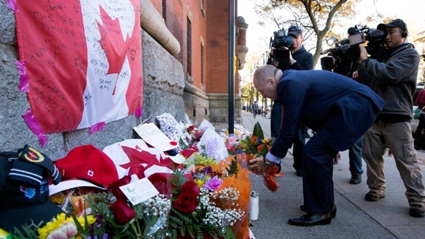 Oct. 23, 2014: Bruce Heyman, the American Ambassador to Canada, places flowers at a makeshift memorial to Cpl. Nathan Cirillo outside of The Lieutenant-Colonel John Weir Foote Armoury in Hamilton, Ontario.