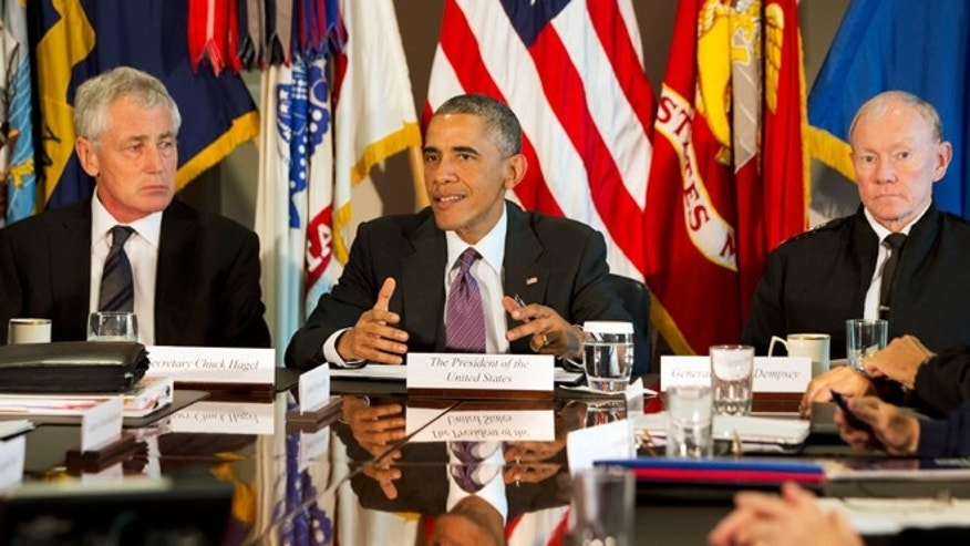 President Obama, flanked by Defense Secretary Chuck Hagel, left, and Joint Chiefs Chairman Gen. Martin Dempsey, speaks to the media at the conclusion of a meeting with senior with senior military leadership, Wednesday, Oct. 8, 2014, at the Pentagon.