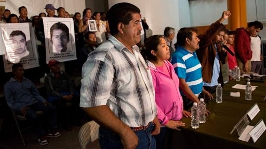 Parents of missing students, some holding pictures of the missing, attend the press conference after a meeting with Mexico's President Enrique Pena Nieto in Mexico, City, Wednesday Oct. 29, 2014. President Enrique Pena Nieto met with parents of 43 teachers college students Wednesday for the first time since they disappeared over a month ago, when investigators say police detained the students and handed them over to a drug gang. (AP Photo/Eduardo Verdugo)