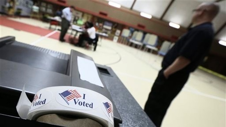 FILE - In this May 20, 2014 file photo, a roll of stickers sits on a ballot box at a Little Rock, Ark. polling place.  (AP Photo/Danny Johnston, File)