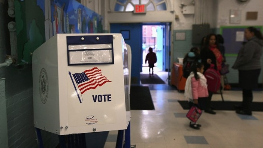 NEW YORK, NY - NOVEMBER 05:  A voting booth stands at the ready as students return to school on November 5, 2012 in the East Village neighborhood of New York, United States. Students at Public School 188, like most schools in New York City, returned to class Monday for the first time since the hurricane hit last week. Many students in the area were displaced due to storm flooding. The school will be used as a polling center in Tuesday's Presidential election.  (Photo by John Moore/Getty Images)