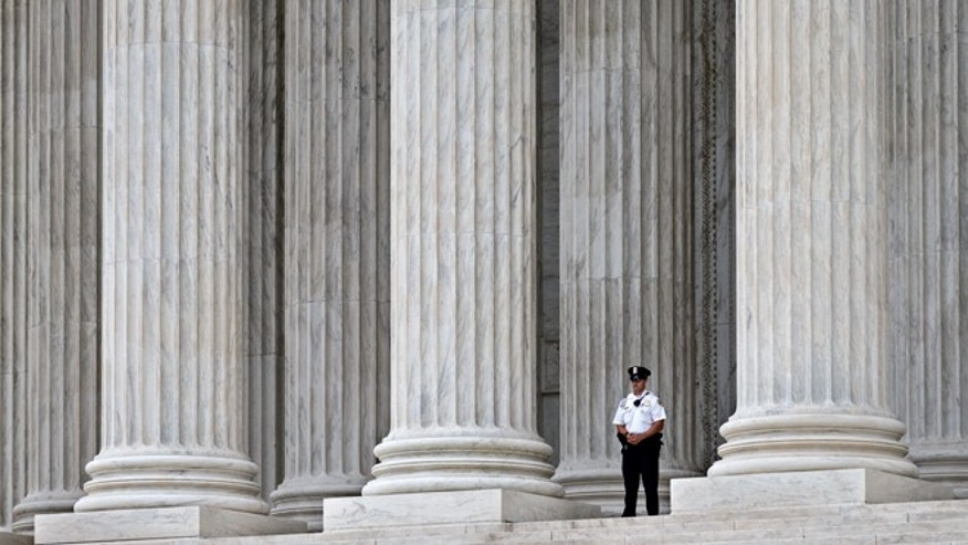 Oct. 7, 2014: A police officer is dwarfed amid the marble columns of the Supreme Court in Washington.