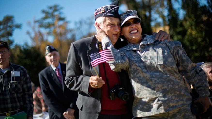Nov. 11, 2014: U.S. Army Georgia National Guard Staff Sgt. Tracy Smith, right, a veteran of the wars in Iraq and Afghanistan, embraces Korean War veteran Jim Conway, 84, as military service members are asked to sing along to the Armed Services Medley during a Veterans Day ceremony at the Atlanta History Center.