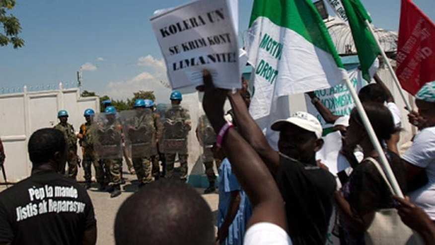 "FILE -- March 22, 2013: A demonstrator holds up a sign that reads in Creole ""Cholera of U.N. is a crime against humanity"" during a protest against the United Nations peacekeeping mission in Port-au-Prince, Haiti."