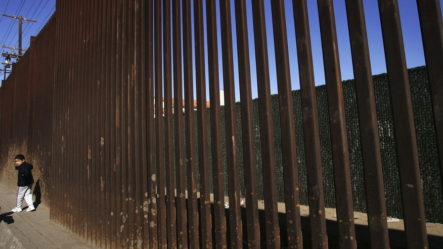 MEXICALI, BAJA CALIFORNIA - MARCH 25:  A boy walks along the US/Mexico border fence on March 25, 2005 in Mexicali, Baja California, Mexico. Since the launch of the North American Free Trade Agreement in 1995, two-way trade has boomed between the US and Mexico, and Mexican dollars are fueling development in economically-depressed Calexico, California. Border communities are now growing increasingly worried that the recent economic gains may be lost as the Bush administration's efforts to tighten security in order to prevent terrorists or their weapons from crossing the border could slow the wheels of commerce. (Photo by David McNew/Getty Images)