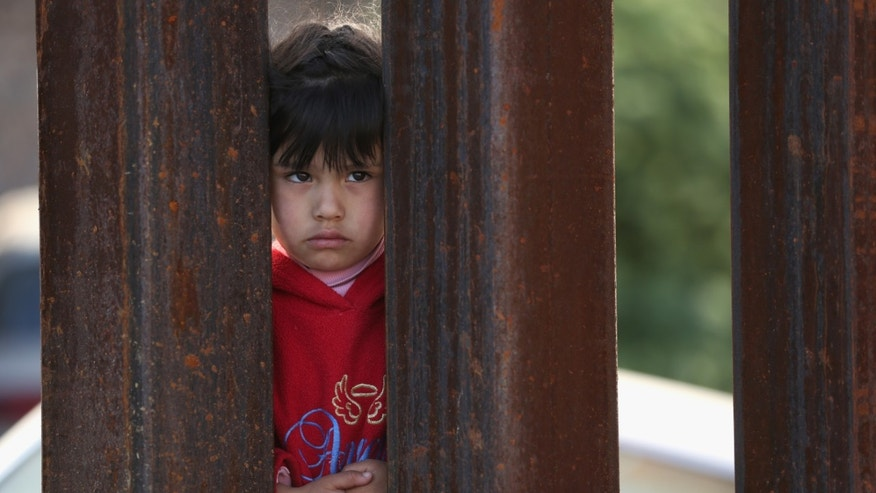 NOGALES, AZ - APRIL 01:  A child on the Mexican side of the U.S.-Mexico border fence looks into Arizona during a special 'Mass on the Border' on April 1, 2014 in Nogales, Arizona. Catholic bishops led by the Archbishop of Boston Cardinal Sean O'Malley held the mass at the border fence to pray for comprehensive immigration reform and for those who have died along the border.  (Photo by John Moore/Getty Images)