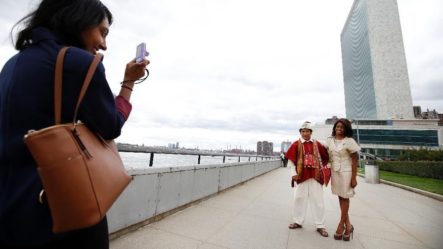Tomas Mamani, of La Paz, Bolivia, left, poses for a photo with Nyasha Zimucha, a native of South Africa now living in New York, outside United Nations headquarters, Monday, Sept. 22, 2014.  The World Conference on Indigenous Peoples began Monday at the U.N. (AP Photo/Jason DeCrow)