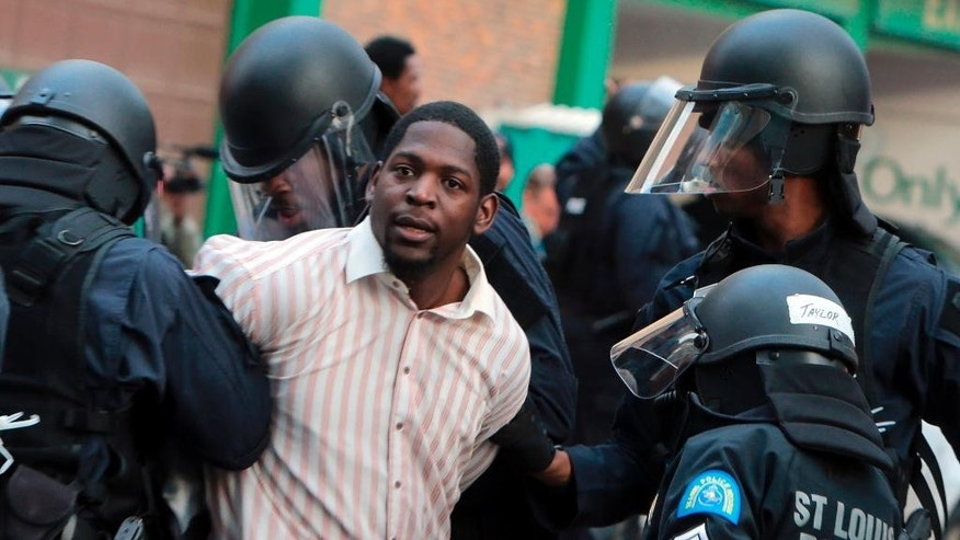 Police arrest protester Derrick Robinson, Sunday, Nov. 30, 2014, in St. Louis.