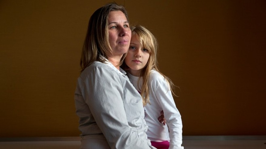 FILE -- Nov. 14, 2014: Peggy Young, of Lorton, Va., with her daughter Triniti, 7, in Washington. Young was pregnant when the company told her she could not have a temporary assignment to avoid lifting heavy packages, as her doctor ordered. She sued UPS for discriminating against pregnant women and, after losing two rounds in lower courts, the Supreme Court will hear her case on December 3.