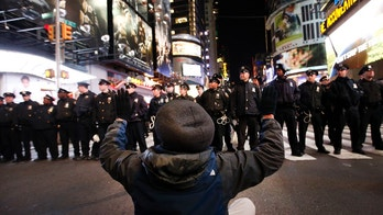 A protester sits in the road while rallying against a grand jury's decision not to indict the police officer involved in the death of Eric Garner encountering a line of police as they make their way west on 42nd Street near Times Square, Thursday, Dec. 4, 2014, in New York. (AP Photo/Jason DeCrow)