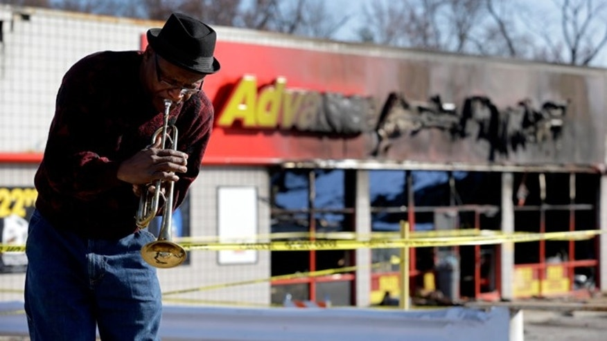 Nov. 28, 2014: Eugene Gillis plays Christmas carols on his trumpet along a section of West Florissant Avenue that saw heavy damage in Ferguson, Mo. The section of road has been closed, but reopened Friday, after many business were damaged after a grand jury decided not to indict a Ferguson police officer in the shooting death of Michael Brown.