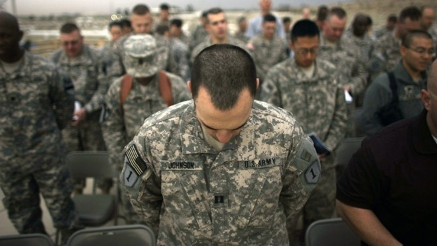 FILE -- U.S. Army soldiers bow their heads in prayer during Easter sunrise service at Camp Liberty in Iraq, in 2009.