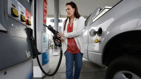 FILE -- Nov. 12, 2014: Lydia Holland replaces the gas nozzle after filling up at a gas station in Sacramento, Calif.