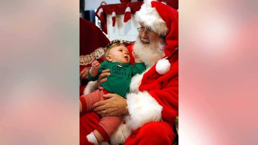 "Dec. 13, 2014: Ricky Bundy, 10 months old, tugs on Santa's beard at a ""Breakfast with Santa"" event in Forest Park, Ill. The event is organized by the local park district."