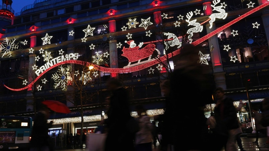 Shoppers carry bags with gifts outside a department store decorated with lights depicting Santa Claus and reindeer in Paris. Kim Komando has tips on five smartphone apps that will lead to the best deals this holiday season.