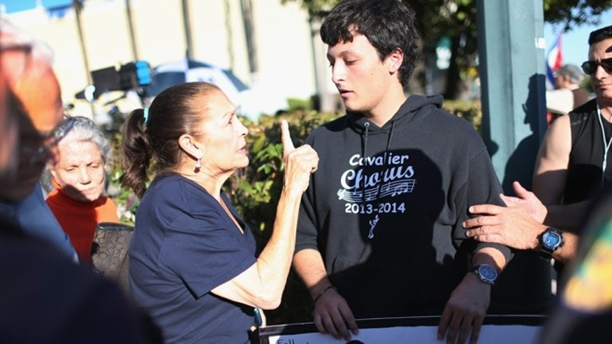MIAMI, FL - DECEMBER 17:  Miriam Clemente speaks with Bryan Medina (R) as he debates her about the new policy laid out by President Barack Obama as they joined people gathered outside the Little Havana restaurant Versailles on December 17, 2014 in Miami, United States.  The president annouced he wants to normalize relations with Cuba.  (Photo by Joe Raedle/Getty Images)