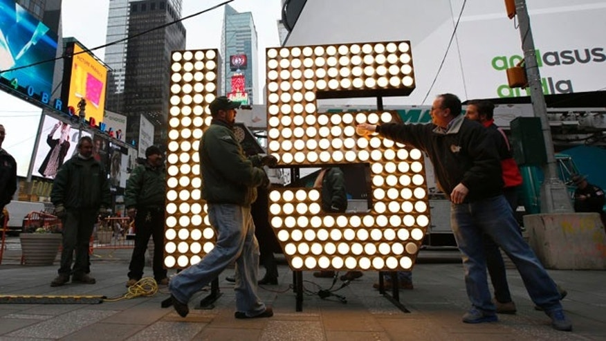 "Dec. 16, 2014: Jeffrey Strauss, right, president of Countdown Entertainment, lights the New Year's Eve ""15"" numerals in a ceremony after they were unloaded from a truck in Times Square in New York."