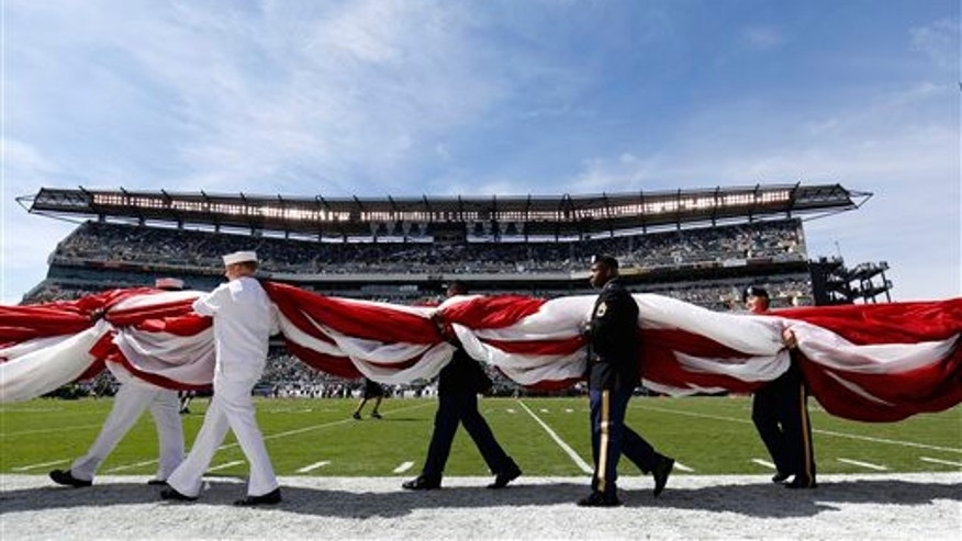 FILE -- Sept. 15, 2013: Military personnel carry an American flag on to the field before an NFL football game between the Philadelphia Eagles and the San Diego Chargers in Philadelphia.