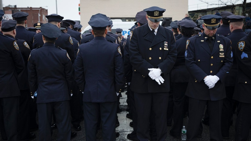 Police officers, left, turn their backs to Mayor de Blasio during the funeral of NYPD Officer Wenjian Liu, Jan. 4, 2015.