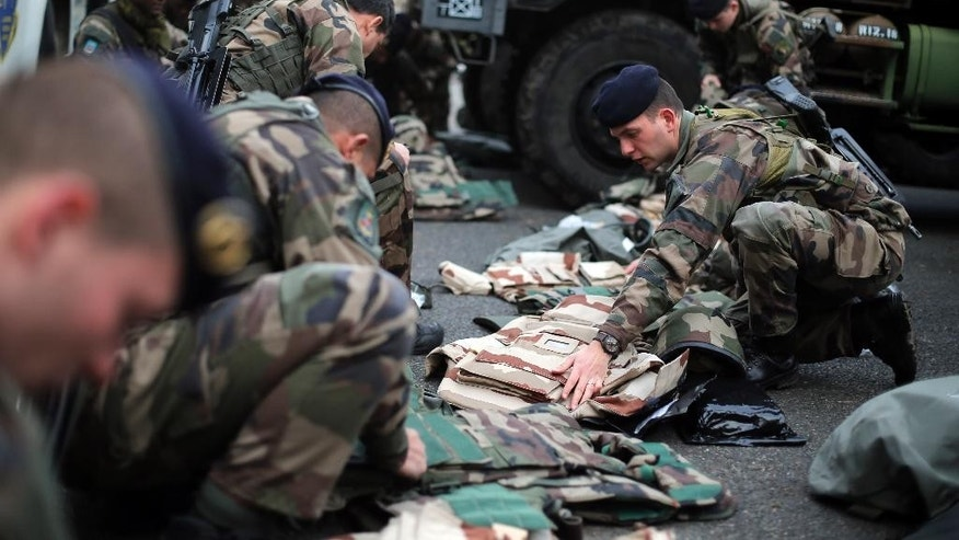 French soldiers prepare before patrolling, at the Satory military camp in Versailles, west of Paris, Tuesday, Jan. 13, 2015. France on Monday ordered 10,000 troops into the streets to protect sensitive sites after three days of bloodshed and terror, amid the hunt for accomplices to the attacks that left 17 people and the three gunmen dead. (AP Photo/Christophe Ena)