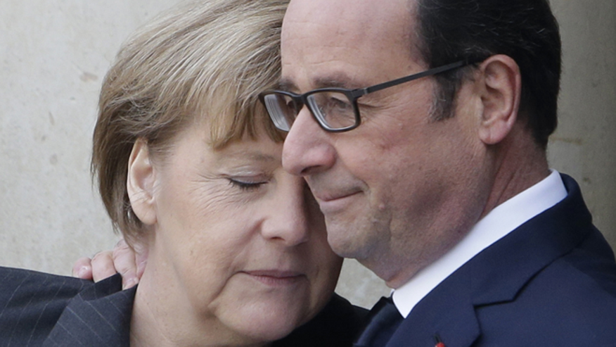 FILE --  Jan. 11, 2015: French President Francois Hollande embraces German Chancellor Angela Merkel, left, as she arrives at the Elysee Palace, Paris. A rally of defiance and sorrow, protected by an unparalleled level of security, on Sunday will honor the 17 victims of three days of bloodshed in Paris that left France on alert for more violence.