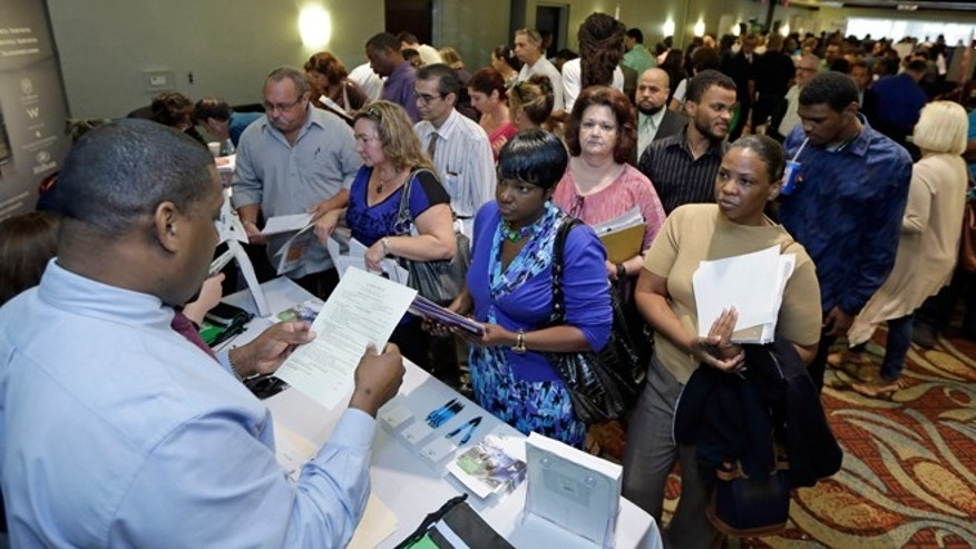 FILE -- Oct. 22, 2014: Russell Neal, left, gives job information to job seeker Queena Moise, foreground second from right, at a job fair in Miami Lakes, Fla.