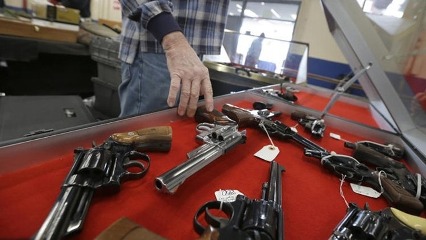 FILE -- Feb. 6, 2015: A dealer arranges handguns in a display case in advance of a show at the Arkansas State Fairgrounds in Little Rock, Arkansas.