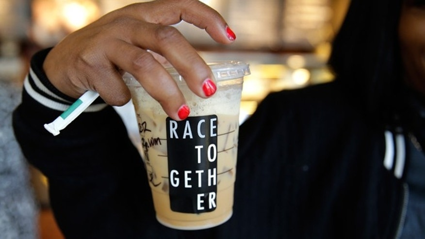 "March 18, 2015: Larenda Myres holds an iced coffee drink with a ""Race Together"" sticker on it at a Starbucks store in Seattle. Starbucks CEO Howard Schultz announced earlier in the day at the company's annual shareholder meeting that participating baristas at stores in the U.S. will be putting the stickers on cups and also writing the words ""#RaceTogether"" for customers in an effort to raise awareness and discussion of race relations."