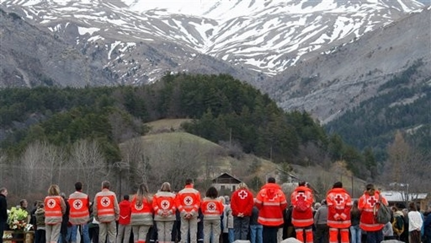 French Red Cross members pay tribute March 28, 2015, to the victims of a Germanwings plane crash in front of a stone slab erected as a monument in Le Vernet, France. (AP Photo/Claude Paris)