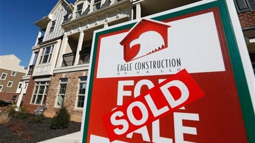 FILE - In this Jan. 8, 2015 photo, a sign with a sold sticker is posted in front of a row of new townhomes in Richmond, Va. Mortgage giant Freddie Mac on Thursday, March 26, 2015 said the national average for a 30-year fixed-rate mortgage declined to 3.69 percent from 3.78 percent a week earlier. (AP Photo/Steve Helber, File)