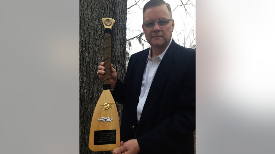 Navy Chaplain Wes Modder is pictured with a ceremonial oar presented to him by Naval Special Warfare Command. He received the oar at the end of his tour.