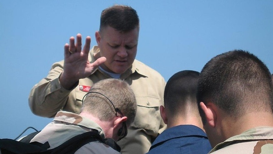 Chaplain Wes Modder prays over Navy service members.