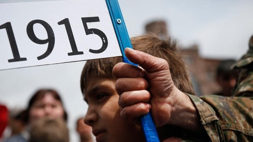"April 24, 2015: An Armenian holds a placard with a sign reading ""1915"", the year of mass killings of Armenians by Ottoman Turks on a city street in Yerevan, Armenia. Armenians on Friday marked the centenary of what historians estimate to be the slaughter of up to 1.5 million Armenians by Ottoman Turks, an event widely viewed by scholars as genocide. Turkey, however, denies the deaths constituted genocide and says the death toll has been inflated."