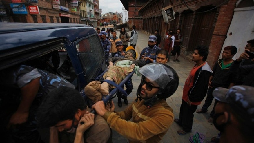 Volunteers carry an injured woman after an earthquake in Kathmandu, Nepal, Saturday, April 25, 2015. A strong magnitude-7.9 earthquake shook Nepal's capital and the densely populated Kathmandu Valley before noon Saturday, causing extensive damage with toppled walls and collapsed buildings, officials said. (AP Photo/ Niranjan Shrestha)