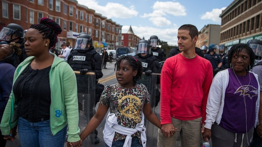 "From left, Adrienne Horton, 11 year-old Shenya Milford, Vinny Bevivino, and Lakia McDaniel, all from Baltimore, Md., gather to sing ""Amazing Grace"" during a gathering of demonstrators after an evening of riots following the funeral of Freddie Gray on Tuesday, April 28, 2015, in Baltimore."
