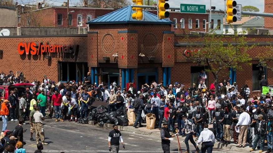 Police and demonstrators gather in the aftermath of rioting following Monday's funeral for Freddie Gray, who died in police custody, on Tuesday, April 28, 2015, in Baltimore.