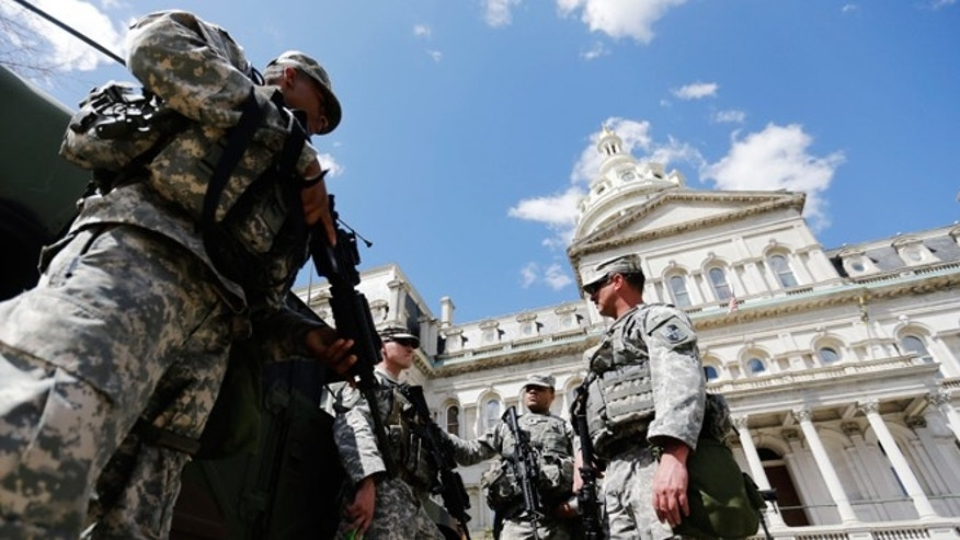 April 29, 2015: Members of the National Guard stand outside City Hall in Baltimore. Schools reopened across the city and tensions seemed to ease Wednesday after Baltimore made it through the first night of its curfew without the widespread violence many had feared. People in Baltimore have been angry over the police-custody death of Freddie Gray.