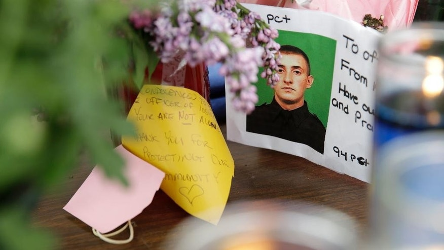 A picture of Brian Moore is displayed amongst flowers and candles at a memorial in front of his precinct house in the Queens section of New York, Tuesday, May 5, 2015.  The 25-year-old Moore died Monday, two days after he was shot. He had been in a coma after undergoing brain surgery.  Demetrius Blackwell will be charged with first-degree murder, prosecutors said. He was charged earlier with attempted murder and other crimes. He is being held without bail and has not entered a plea.(AP Photo/Seth Wenig)