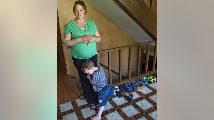 Kateri Schwandt shares a moment with her son, Luke, 3, inside their Rockford, Mich., home Wednesday, May 6, 2015. Schwandt and her husband, Jay, have 12 boys. They are expecting a baby on May 9, the day before Mother's Day, and they're sticking to their tradition of not finding out in advance whether they're having a boy or girl. (Chris Clark/The Grand Rapids Press via AP)