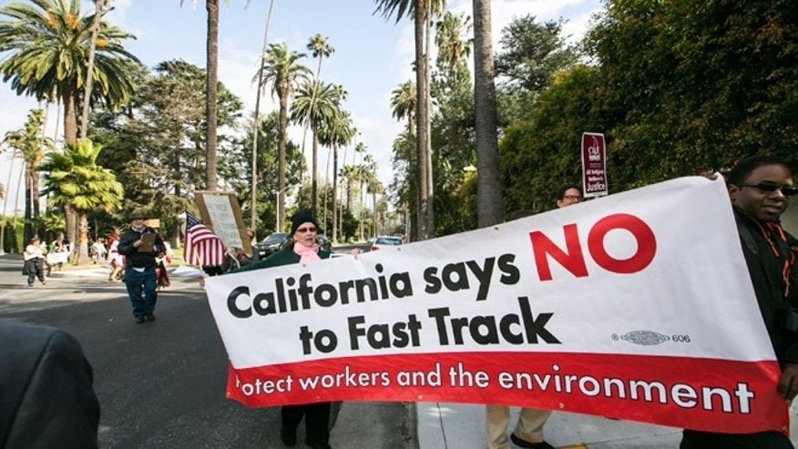 "May 7, 2015: Los Angeles community members take to the streets of Beverly Hills to demand that Hillary Rodham Clinton oppose the Trans-Pacific Partnership (TPP) and Trade Promotion Authority (TPA) known as ""The Fast Track,"" in Beverly Hills, Calif. AP Photo/Damian Dovarganes"