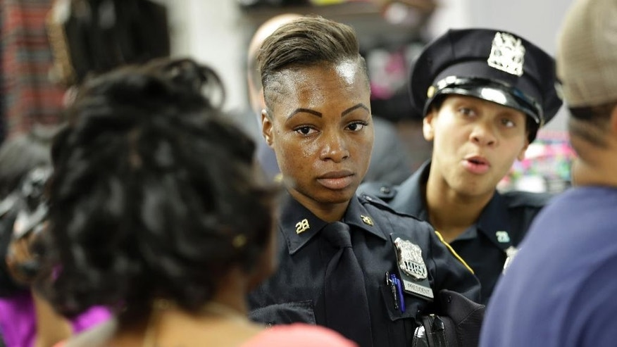 Police officers Shakara President, center, and Lanora Moore talk with an unhappy customer inside a store on 125th Street in the Harlem section of New York, Wednesday, April 29, 2015. (AP Photo/Seth Wenig)