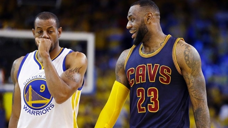 Cleveland Cavaliers forward LeBron James (23) smiles next to Golden State Warriors forward Andre Iguodala (9) during the second half of Game 2 of basketball's NBA Finals in Oakland, Calif., Sunday, June 7, 2015. (AP Photo/Ben Margot)