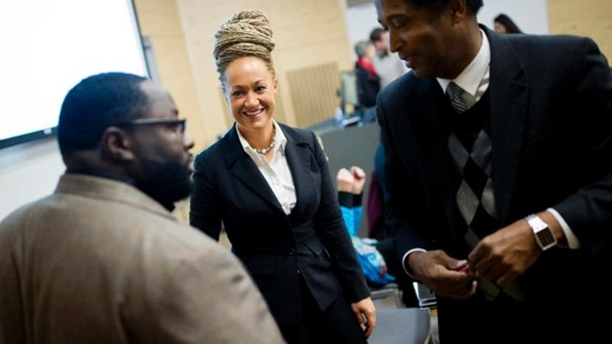 FILE- In this Friday, Jan. 16, 2015 file photo, Rachel Dolezal, Spokane's newly elected NAACP President, smiles as she meets with Joseph M. King of King's Consulting, left, and Dr. Scott Finnie, director and senior professor of  EWU's Africana Education Program before the start of a Black Lives Matter Teach-In on Public Safety and Criminal Justice  at EWU in Cheney, Wash.  (Tyler Tjomsland/The Spokesman-Review via AP, File) COEUR D'ALENE PRESS OUT