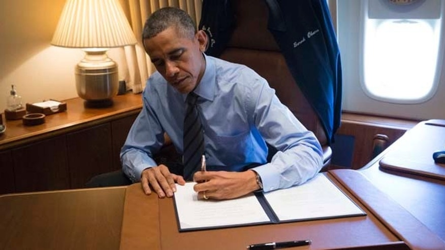 FILE - November 21, 2014: President Obama signs two Presidential Memoranda associated with his Executive Actions on immigration from his office on Air Force One upon his arrival in Las Vegas Nevada.