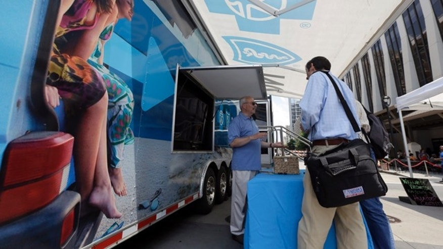 FILE - In this photo taken Wednesday, July 17, 2013, Blue Cross Blue Shield of North Carolina employee Lew Borman, left, helps a customer outside a trailer at the downtown farmer's market in Raleigh, N.C. (AP Photo/Gerry Broome, File)