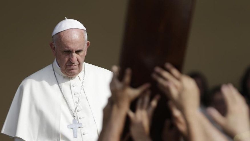 Pope Francis waits for a group of young people carrying a wooden cross during a meeting with the youths, in Turin, Italy, Sunday, June 21, 2015. Pope Francis earlier prayed in front of the Holy Shroud, the 14 foot-long linen revered by some as the burial cloth of Jesus, on display at the Cathedral of Turin.