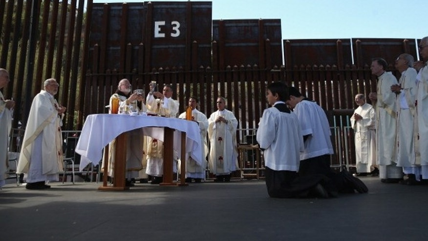 NOGALES, AZ - APRIL 01:  Archbishop of Boston Cardinal Sean O'Malley (L), and fellow Catholic clergy stand next to the U.S.-Mexico border fence during a special 'Mass on the Border' on April 1, 2014 in Nogales, Arizona. Catholic bishops led by Cardinal O'Malley held the mass at the border fence to pray for comprehensive immigration reform and for those who have died along the border.  (Photo by John Moore/Getty Images)